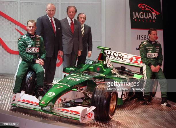 Drivers Johnny Herbert and Eddie Irvine sit on the wheels of the new Jaguar R003 Formula One racing car unveiled in London on the day former F1...