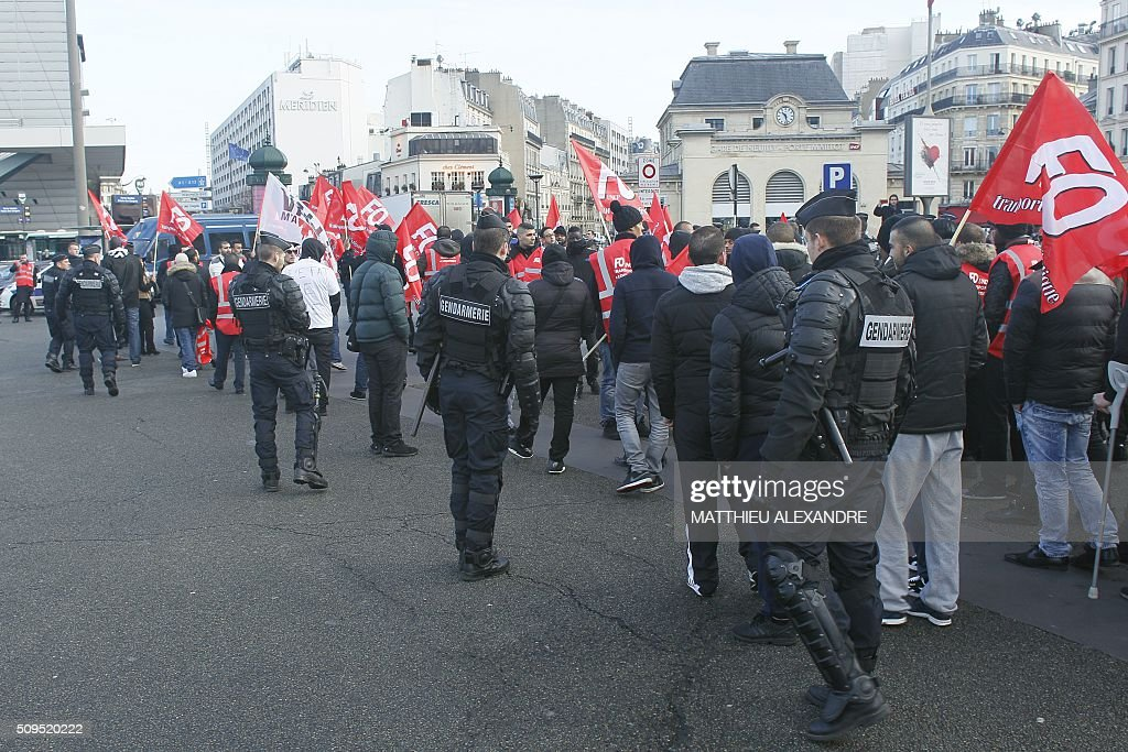 Drivers of Uber and other ride-hailing companies, known in France as 'voitures de tourisme avec chauffeur' (VTC), a class of companies that allow passengers to book rides with independent professional chauffeurs, are escorted by policemen as they gather at Porte Maillot in Paris on February 11, 2016, to defend jobs they believe are threatened by measures the government recently announced in favor of taxis. / AFP / MATTHIEU ALEXANDRE
