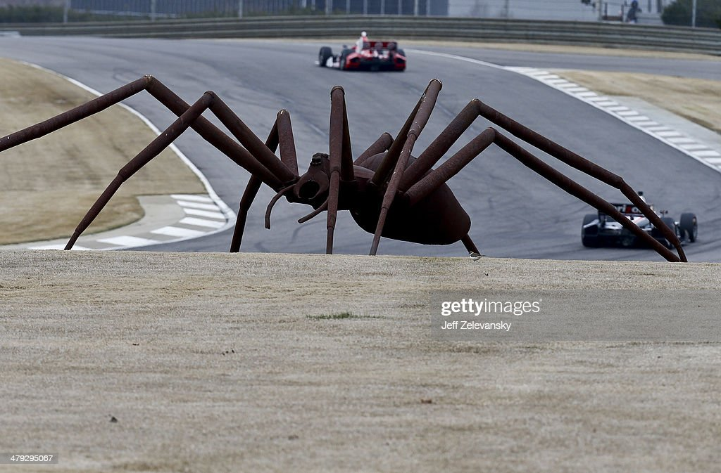 Drivers pass a massive spider sculpture during IndyCar testing at Barber Motorsports Park on March 17 2014 in Birmingham Alabama