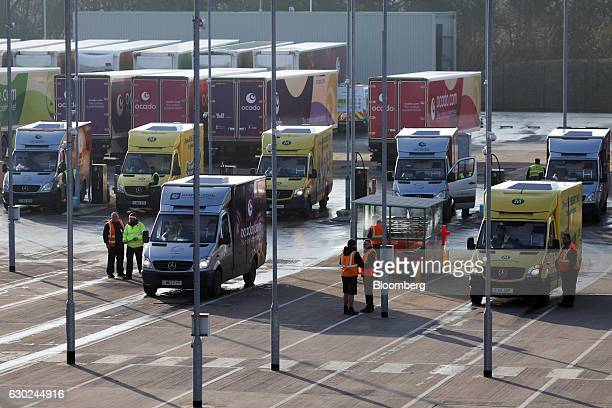 Drivers prepare to climb into Ocado and Wm Morrisons Supermarkets Plc branded delivery vehicles at the Ocado Group Plc distribution centre in Dordon...