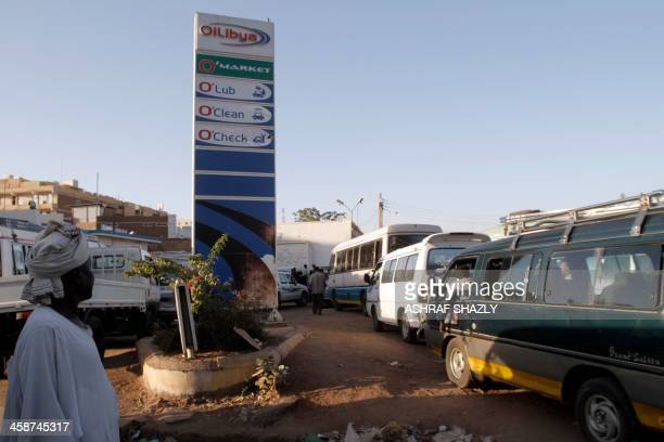 Drivers queue up in their vans for fuel at a gas station in the Sudanese capital Khartoum on December 21 2013 Dozens of buses queued for fuel...