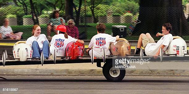 Drivers ride back uphill with their cars after racing in the1999 Greater Washington Soap Box Derby 10 July 1999 in Washington DC The race which was...