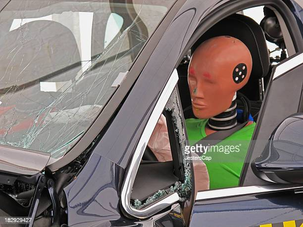 Driver's side view of a car with a crash dummy at the wheel