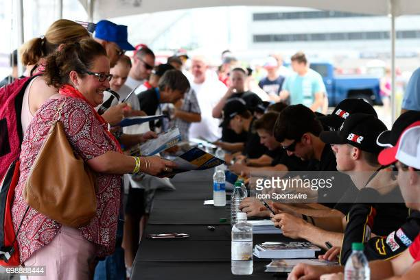 Drivers sign autographs for fans in the infield at the NASCAR Camping World Truck Series Drivin' for Linemen 200 on June 17 at Gateway Motorsports...