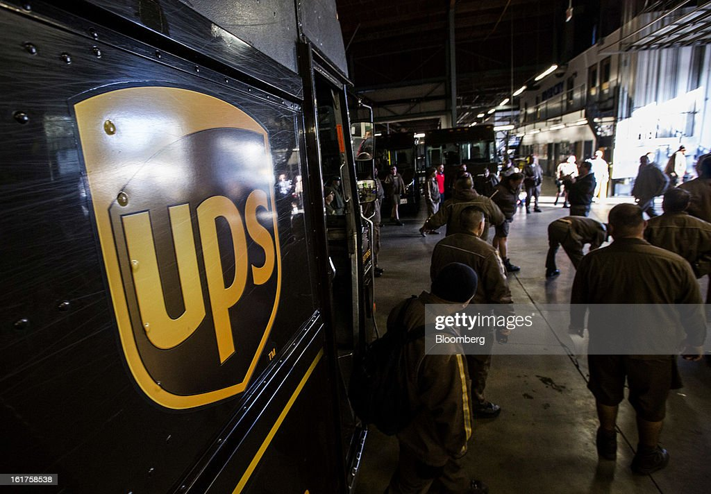 Drivers stretch at a morning meeting before heading out to make deliveries at the United Parcel Service (UPS) distribution center in Sacramento, California, U.S., on Thursday, Feb. 14, 2013. 100 UPS delivery all-electric vehicles, developed by Electric Vehicles International (EVI), have been deployed this week and are said to eliminate the use of 126,000 gallons of fuel per year. Photographer: Ken James/Bloomberg via Getty Images