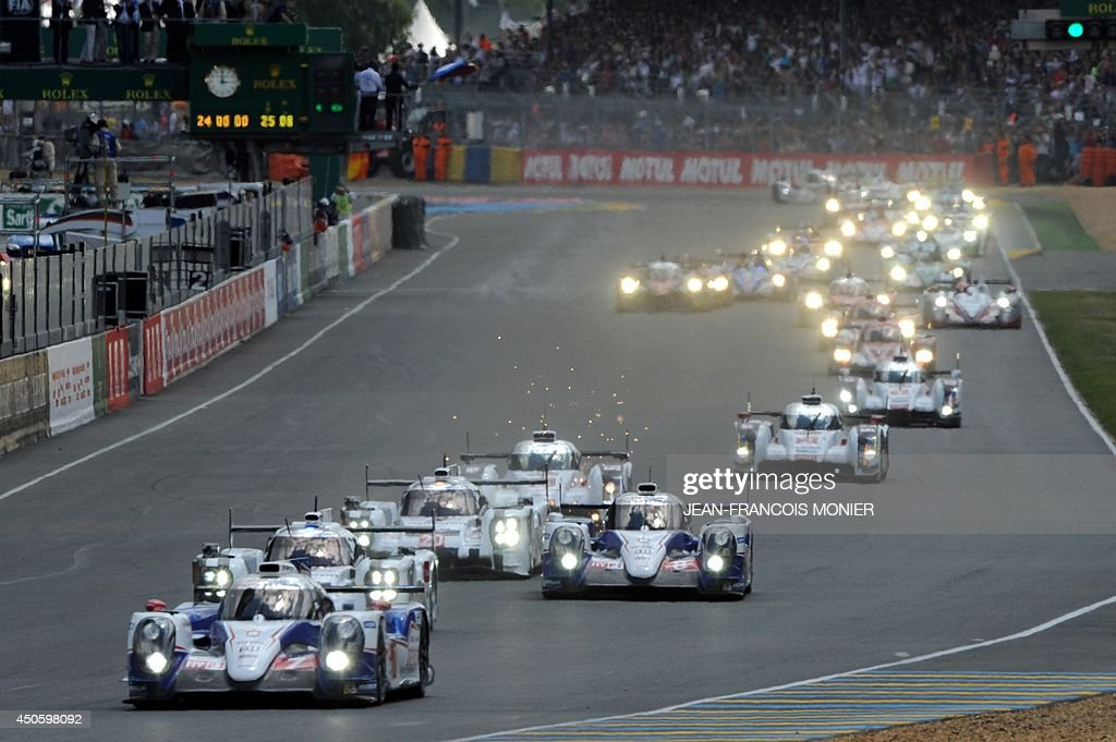 Drivers take the start at the 82nd 24 Hours of Le Mans endurance race in Le Mans western France on June 14 2014 54 cars with162 drivers are...