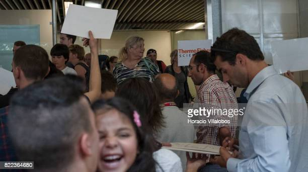 Drivers try to call the arriving passengers attention at arrivals hall in Terminal 1 of the Humberto Delgado International Airport on July 25 2017 in...