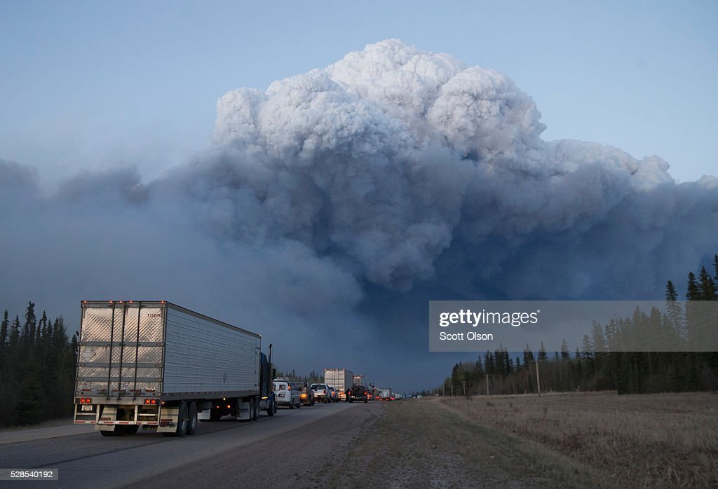 Drivers wait for clearance to take firefighting supplies into town on May 05 2016 outside of Fort McMurray Alberta Wildfires which are still burning...