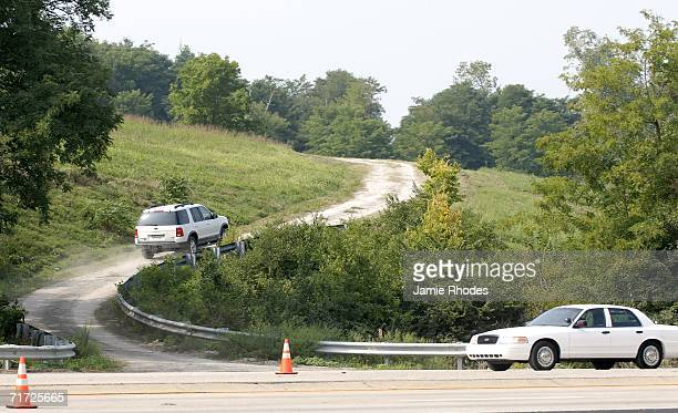 SUV drives up a gravel road to the crash site of Comair Flight 5191 that crashed shortly after departure from Blue Grass Airport August 27 2006 in...