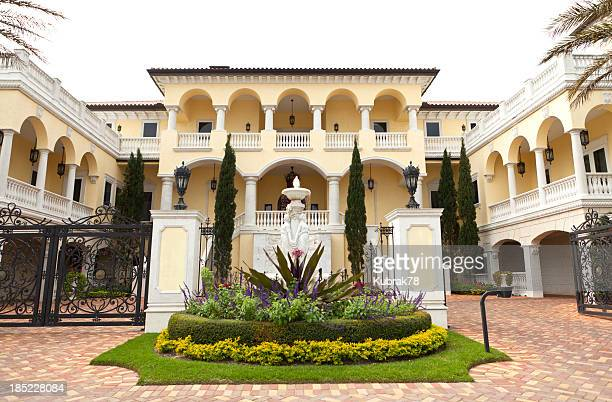 Driveway to luxury two story yellow and White House