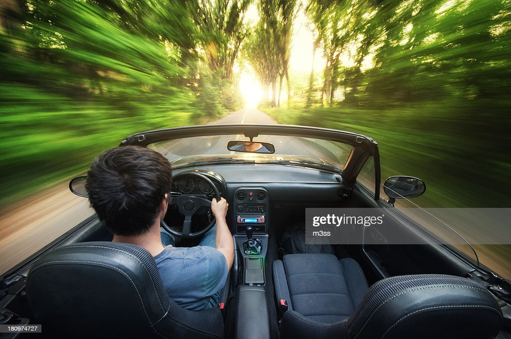 Driving a convertible at sunset