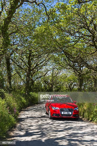 Driving a red German Audi saloon car along country lane at Hartland in North Devon Southern England UK#13#10
