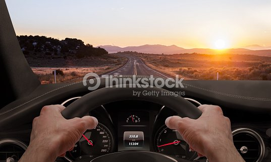 Driving at sunset. View from the driver angle while : Stock Photo