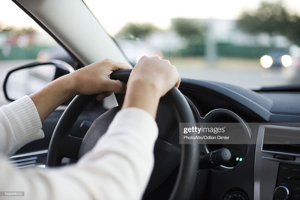 Driving car with both hands on the steering wheel