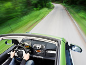 Motion blur shot of a man driving electric car on the mountain road and not polluting the airSee more car driving images in my portfolio