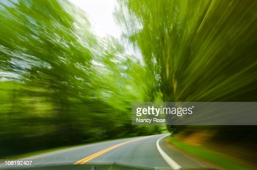 Driving fast on winding road, motion blur of trees