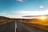 Tourist attraction and campers tour route.Beautiful golden sunset illuminates asphalt road.