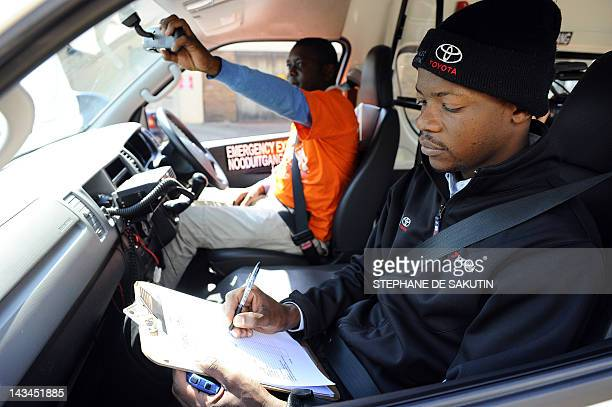A driving instructor evaluates a minibus taxi driver on April 16 in Germiston as other drivers wait their turn as part of a training session...