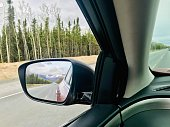 The beautiful mountain close by town of Homer in South of Alaska is pictured in the sideview mirror of my car.