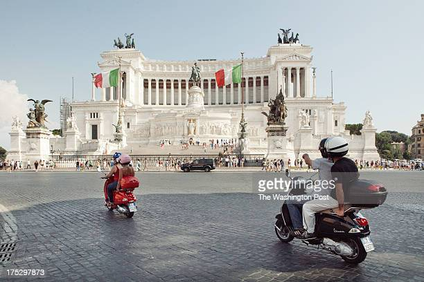 Driving past the National Monument to Victor Emmanuel II in Piazza Venezia Fatima Giorgili rides with Scooteroma's Annie Ojile Nerone as Scooteroma's...