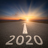 Upcoming 2020 new year on empty highway leading to the mountains through the desert against the rising sun.