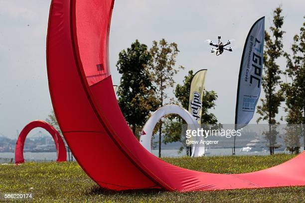 A drone flies through an obstacle course during practice day at the National Drone Racing Championships on Governors Island August 5 2016 in New York...