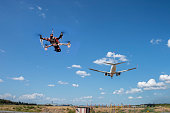 A drone flying near an airport. It is illegaly to fly drones near airport. This is a composite image to serve as a concept.