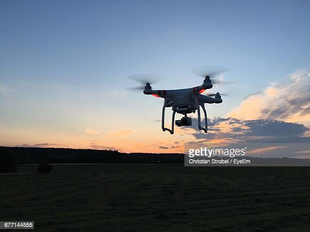 Drone Flying Over Field During Sunset