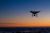 Drone flying over ocean at dawn