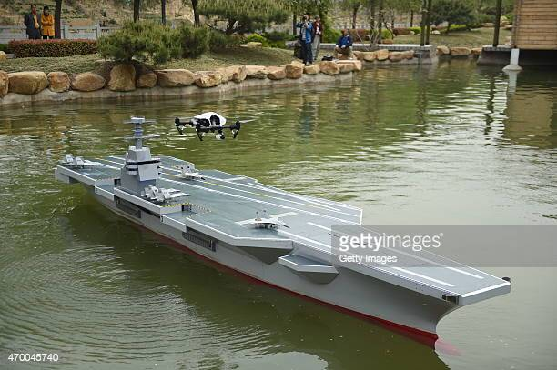 A drone lands on a 6meterlong and 80centimeterwide scale model aircraft carrier weighing more than 700 kilograms as it is tested in water on April 17...