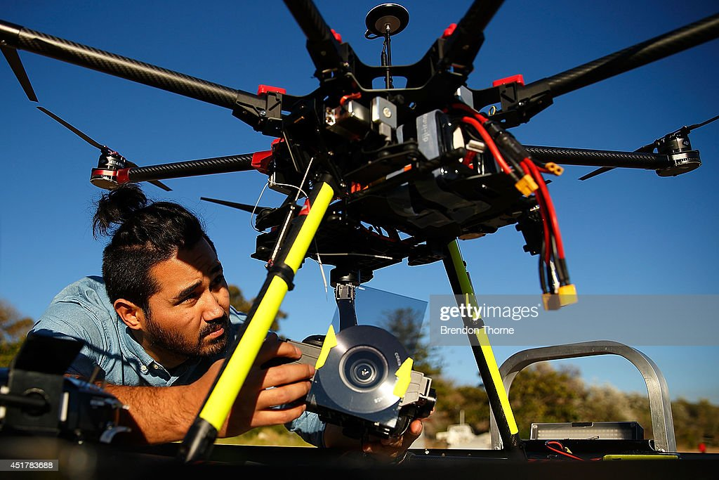 Drone operator, Ken Butti carries out pre-flight checks of the custom built DJI s1000 Drone prior to flight at Palm Beach on July 4, 2014 in Sydney, Australia. Commercial and recreational UAV (Unmanned Aerial Vehicles) sales in Australia have regulators concerned about safety, privacy and security, while the commercial industries of mining, farming, property, and sport are embracing the new technology. Under the current CASA (Civil Aviation Safety Authority) regulations all unmanned aircraft weighing more than 2kg need to have a UAS operators certificate. Licensed operators are not allowed to fly above 400ft, not within 5km of an airfield boundary and can't fly within 30 metres of people not involved with the operation.