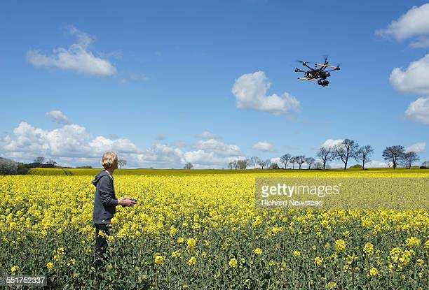 Drone Pilot Flying Over Rapeseed Field