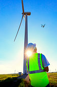 Drone pilot wearing his safety vest operating a UAV on Kansas wind farm.