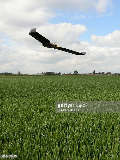 A drone plane flies over a crop field on May 6 2014 in Caulieres northern France during a demonstration of the French Somme department Chamber of...