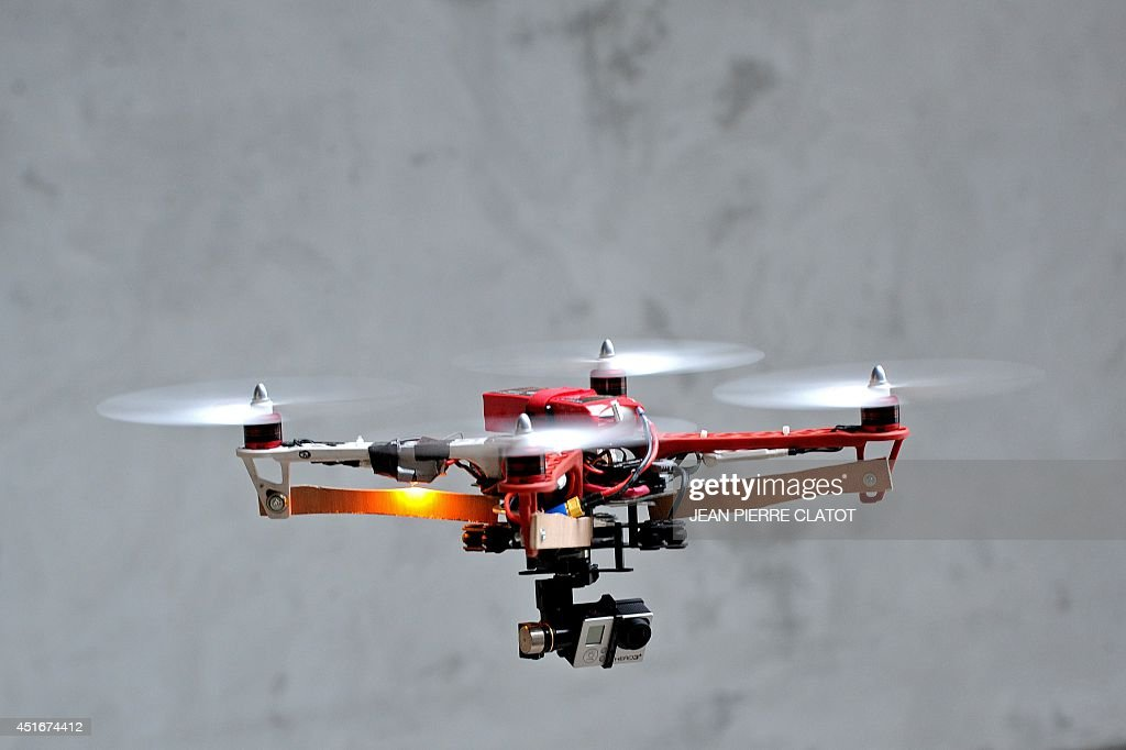 A drone prototype equiped with a GoPro camera is being tested at the headquarters of the start-up Squadrone System on July 2, 2014 in Saint-Martin d'Hères, centraleastern France. The Grenoble-based start-up Squadrone System launched a Kickstarter campaign for the HEXO+, a camera that needs no camera man and can fly and follow whatever target it is given. The campaign reached its $50,000 goal in just one hour, and in less than one day reached its $250,000 stretch goal, which means the company will include live view video feedback in its product. AFP PHOTO / JEAN-PIERRE CLATOT