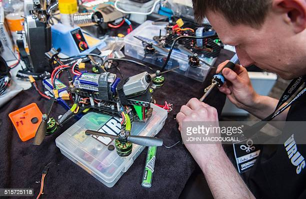 A drone racer works on his drone at the Digital Business fair CEBIT in Hanover central Germany on March 15 2016 This edition of Cebit offers a drone...