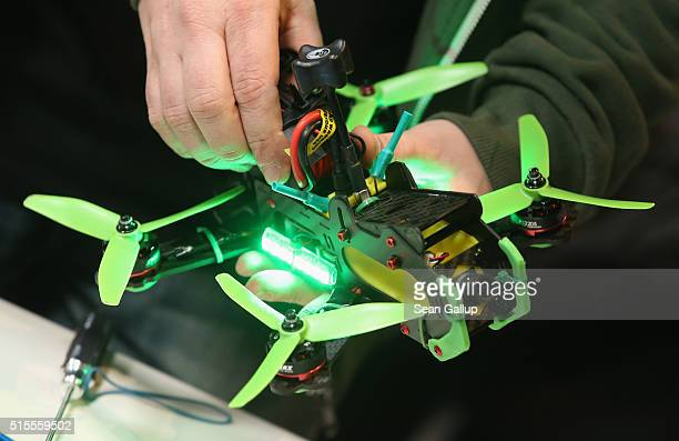 A drone racing enthusiast prepares a small multirotor racing drone in the Dronemasters hall at the 2016 CeBIT digital technology trade fair on the...