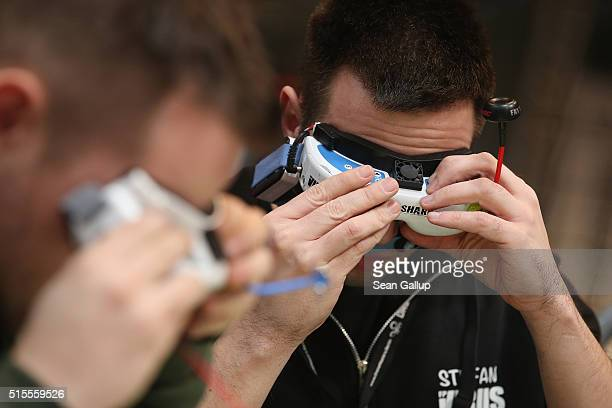 Drone racing enthusiasts prepare their first person view goggles in the Dronemasters hall at the 2016 CeBIT digital technology trade fair on the...