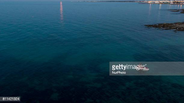 A drone view of a man driving her watercraft during a sunset in Casalabate Italy on July 9 2017 Casalabate is a town on the Adriatic coast in the...