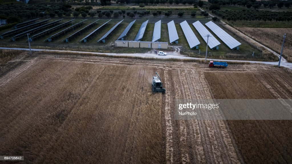A drone view of farmer workers during harvest wheat near a photovoltaic panels in San Pietro Vernotico, South of Italy, on June 10, 2017.