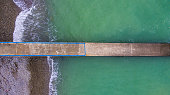 Top-down drone view of the mole in the sea with the pebble beach