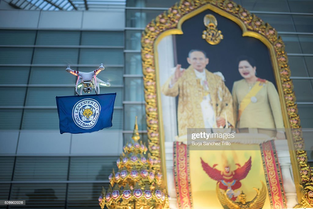 A drone with a Leicester City flag flighs in front of a Thai king's portrait before the Manchester United and Leicester City match on May 1, 2016 in Bangkok, Thailand. Leicester City fans gather at King Power Hotel in Bangkok to watch the Premier League game between Manchester United and Leicester City at Old Trafford.