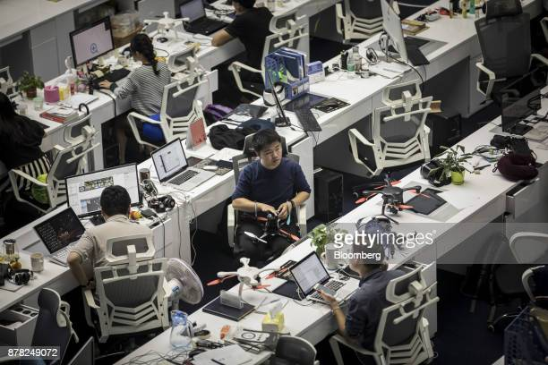 Drones sit on desks as employees work in front of computers in a testing facility at the EHang Inc headquarters in Guangzhou China on Thursday Nov 2...