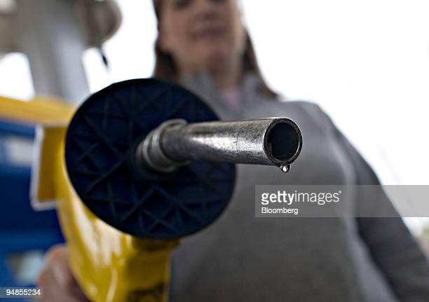 A drop of E85 a mixture of 85 percent ethanol and gasoline hangs at the end of a gas pump held for a photograph by Katie Hitt at a Mobil station in...