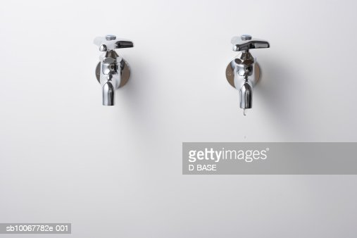 Drop of water falling from faucet : Stock Photo