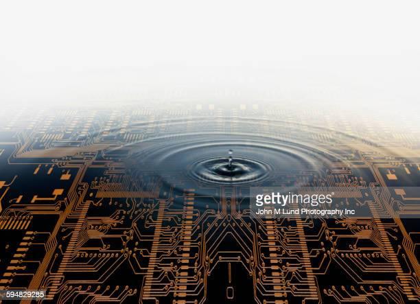 Drop of water rippling in pool over circuit board