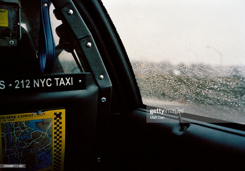 Droplets of rain on taxi cab window, view from inside