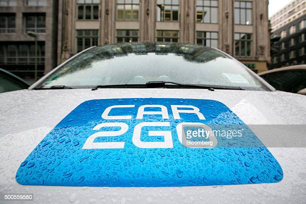 Droplets of rain water rest on the Car2Go carsharing logo as it sits on the hood of a Daimler AG Smart ForTwo automobile in Berlin Germany on...