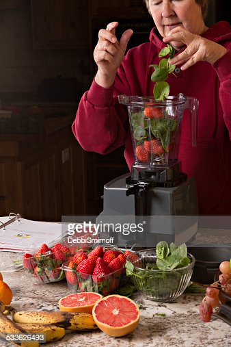Dropping Strawberries And Spinach Into A Juicer