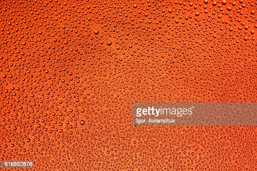 Drops of water on the glass with a red background : Stock Photo